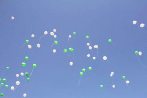 Weiße und grüne Luftballons die in die Luft steigen