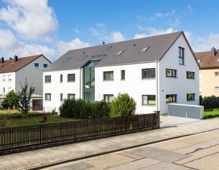 immocontec-Referenz: Blick auf die Hausfront des Mehrfamilienhauses VIO2 in Weichs in Regensburg
