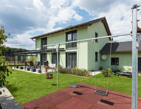 immocontec-Referenz: Garten mit Schaukeln eines Zweifamilienhauses mit Doppelgarage in Poppenricht