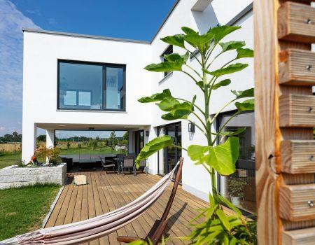 immocontec-Referenz: Außenansicht mit Blick auf die Terrasse eines Einfamilienhaus-Neubaus mit Garage in Neukirchen