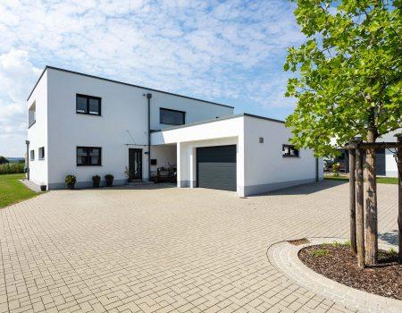 immocontec-Referenz: Außenansicht eines Einfamilienhaus-Neubaus mit Garage in Neukirchen