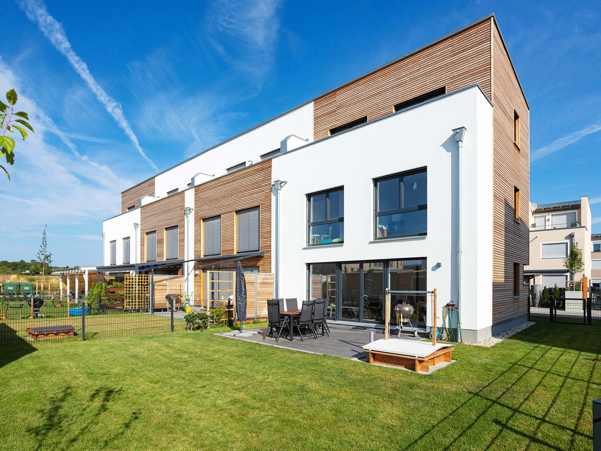immocontec-Referenz: Blick vom Garten auf ein Mehrfamilienhaus in Holzrahmenbauweise in Burgweinting
