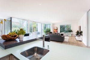 immocontec-Referenz: Blick von der Küche in das Wohnzimmer eines modernen Einfamilienhauses in Regensburg